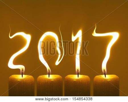 Happy new year 2017, modified photo of four candles. Flames write numbers 2017.