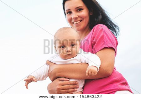 Beautiful Mother And Baby outdoors. Nature. Beauty Mum and her Child playing in Park together. Outdoor Portrait of happy family