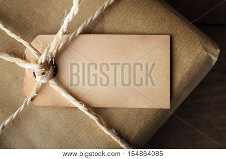 Close Up Of Aged Blank Label On String Tied Parcel