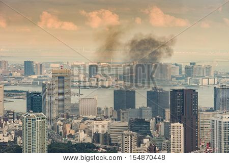Tokyo Japan - September 26 2016: Aerial view since shot off Observatory tower. A black smoke floats over part of Tokyo harbor. Water scapes and multiple highrise buildings under cloud evening sky.
