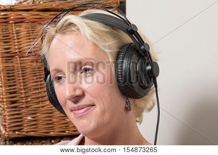 Sitting Blonde Woman Wearing Headphones Tilting Head And Smiling