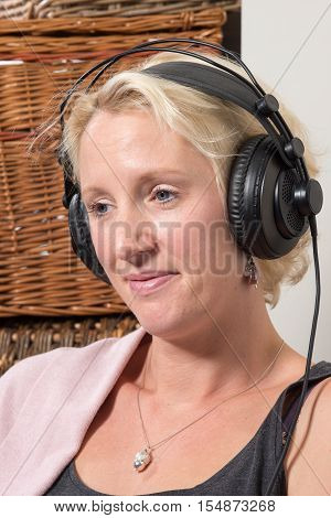 Sitting Blonde Woman At Home Wearing Large Headphones And Smiling