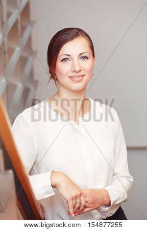 Portrait of beautiful smiling nice young white Caucasian business woman with blue eyes wearing white office blouse shirt dress code looking in camera slavic Russian European face