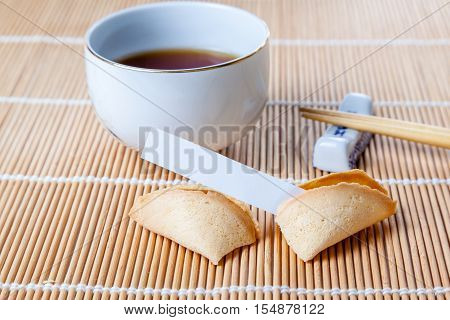 Broken Fortune Cookie With Slip And Chopsticks And Tea