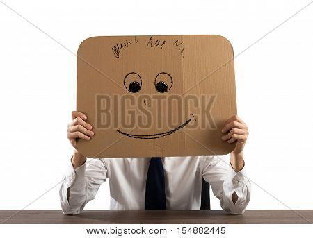 Businessman in the office holds a cardboard with a smiley face
