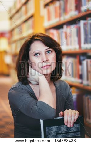 Closeup portrait of thoughtful middle age mature woman student in library looking away from camera teacher librarian profession back to school concept