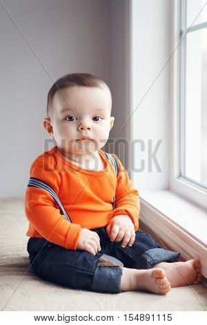 Portrait of cute adorable stylish Caucasian baby boy with black eyes in orange red shirt onesie jeans with suspenders barefoot sitting on windowsill looking in camera natural window light lifestyle