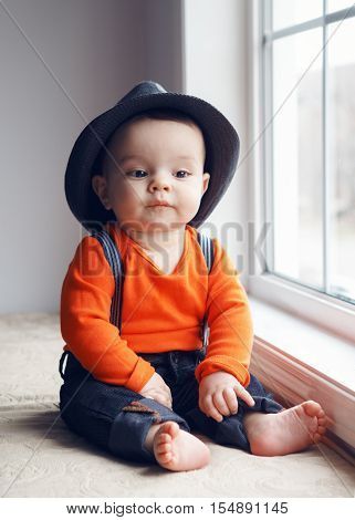 Portrait of cute adorable stylish Caucasian baby boy with black eyes in hat orange shirt onesie jeans with suspenders barefoot sitting on windowsill looking away natural window light lifestyle