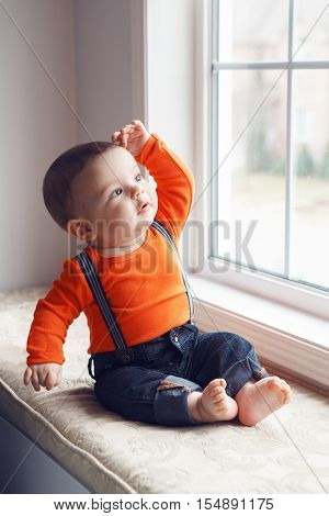 Portrait of cute adorable stylish Caucasian baby boy with black eyes in orange shirt onesie jeans with suspenders barefoot sitting on windowsill looking away touching his head natural window light lifestyle
