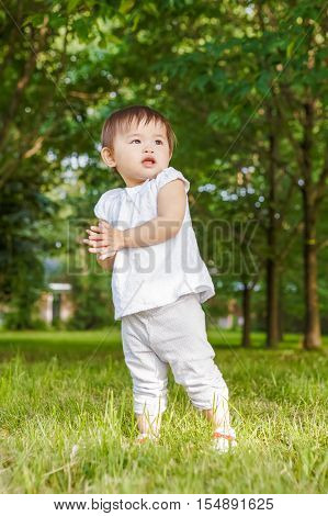 Portrait of cute adorable little Asian girl child baby one year old in white pants shirt standing on field meadow grass on sunset playing clapping her hands