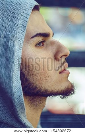Closeup conceptual art portrait of beautiful handsome young middle east brunette man with blue eyes beard wearing blue hoodie outside in street looking away up