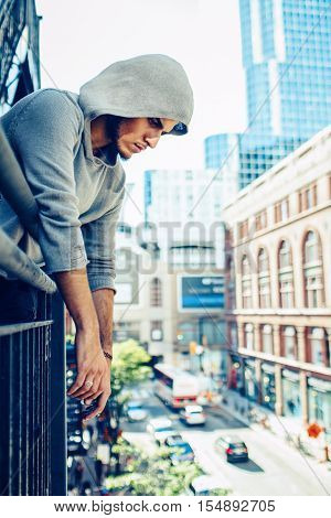 Conceptual art portrait of beautiful handsome pensive sad tired gothic young middle east brunette man with beard in hoodie standing on staircase in city urban looking down on street