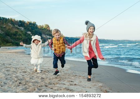 Group portrait of three funny smiling laughing white Caucasian children kids friends playing running on ocean sea beach on sunset outdoors happy lifestyle childhood concept