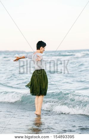 Portrait of beautiful Caucasian white brunette woman with short hair in grey shirt green olive tutu tulle skirt standing barefoot on beach in sea water her back to camera free happy lifestyle