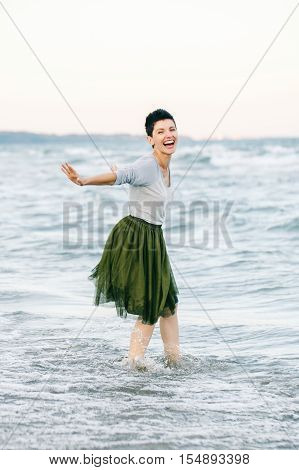 Portrait of beautiful smiling laughing Caucasian brunette woman with short hair in grey shirt green olive tutu tulle skirt standing barefoot on beach in sea water looking in camera free happy lifestyle