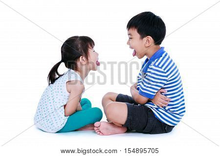 Bad behavior. full body of asian children sticking out tongues and mocking each other. Sister and brother sitting at studio isolated on white background.