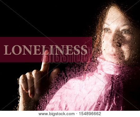 loneliness written on virtual screen. young woman melancholy and sad at the window in the rain, her neck warm scarf.