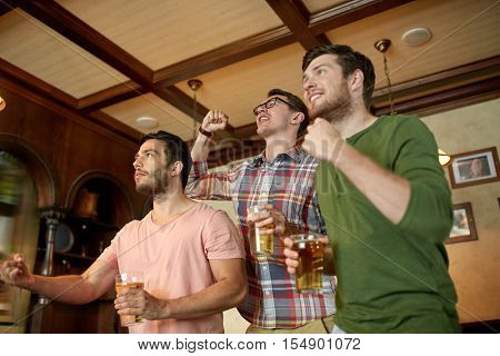 people, leisure, friendship and sport concept - happy male friends or fans watching sport game or football match and drinking beer at bar or pub