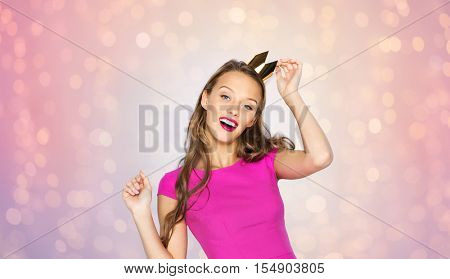 people, holidays and fashion concept - happy young woman or teen girl in pink dress and princess crown over rose quartz and serenity lights background