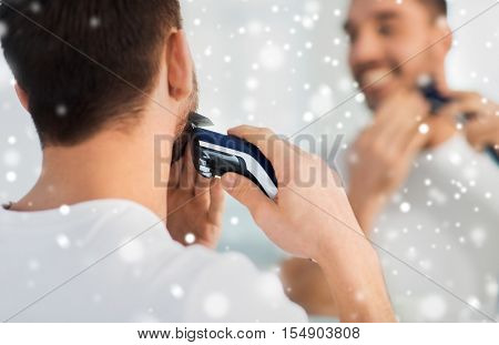 beauty, shaving, grooming and people concept - close up of young man looking to mirror and shaving beard with trimmer or electric shaver at home bathroom over snow