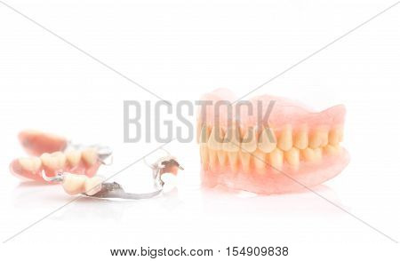 Dirty denturesTartar on full dentures and partial dentures on white background