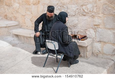 KIDRON VALLEY, ISRAEL - MARCH 5, 2011: Orthodox monk and parishioner woman at Holy Lavra of Saint Sabbas the Sanctified, known in Arabic as Mar Saba