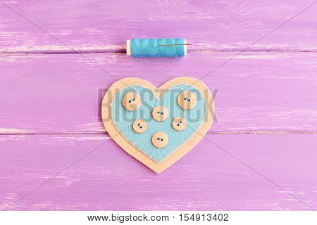 How to sew a felt heart decor. Step. Sew buttons with a blue thread on one side of a felt heart. Blue thread, needle on wooden background. Souvenir for Valentine's day, wedding, mother's day