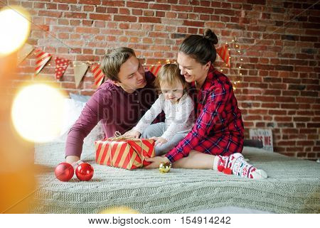 Christmas morning. The daddy and mum give daughter the Christmas gift in bright packing. Little girl with interest looks at a box. Room is festively decorated. Merry Christmas and a Happy New Year.