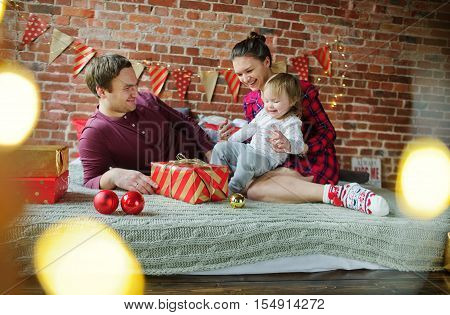 Christmas morning. Young family gleefully congratulates each other Merry Christmas. On bed there are many Christmas gifts in bright packings and Christmas-tree decorations. Merry Christmas. Happy New Year