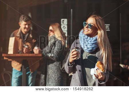Beautiful young blonde woman in glasses holding coffee cup and croissant and looking at sun with smile while standing outdoor. The weather is great today to walk with friends!