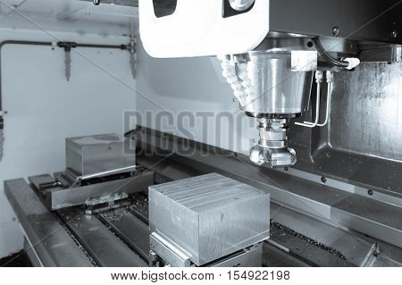 The face milling tool with the raw material work piece on the CNC milling machine in the silver tone effect.
