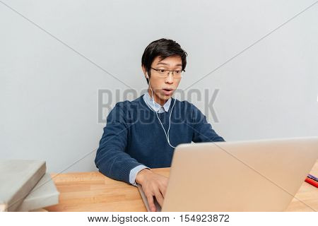 Close up of asian student sits by the table. surprised