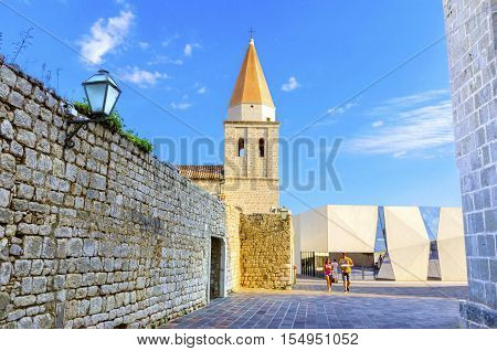 Krk town, Krk, Croatia - 22 August, 2015: The pyramidal tower of the Church of our Lady of Health a romanesque cathedral formerly named St Michael the archangel basilica at the Square of the The Glagolitic housed monasteries on Krk island in Croatia and t
