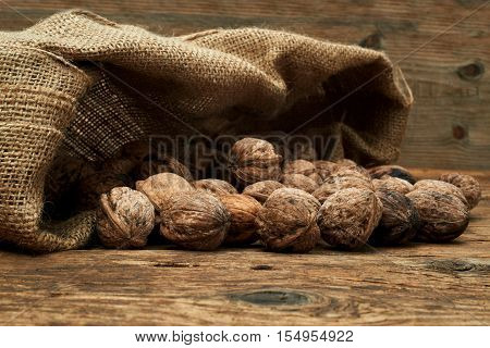 Walnuts in a burlap bag on a wooden background.