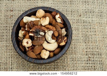 Bowl of mixed nuts on a burlap background.