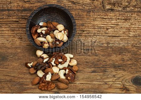 Bowl of mixed nuts on wooden table.