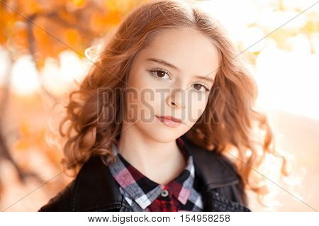 Beautiful blonde girl with long curly hair 12-14 year old wearing stylish jacket outdoors over autumn nature background. Looking at camera.