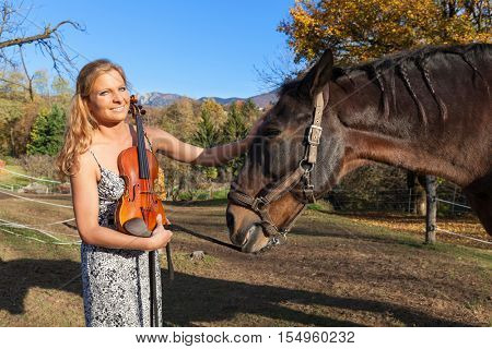 portrait of violinist with a horse, scene at a farm