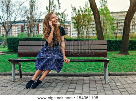 Cute girl sitting on the bench and talking on the phone and laughing in the park zone of the city. Social concept.