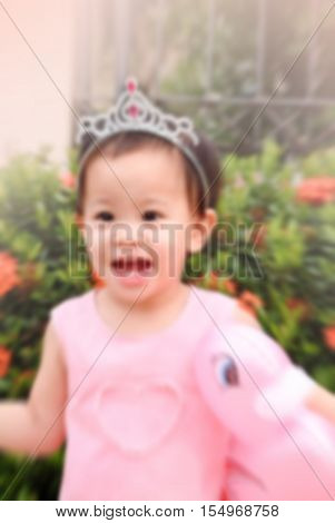 de-focused cute little girl with pink duck doll in hand and pink dress and diadem