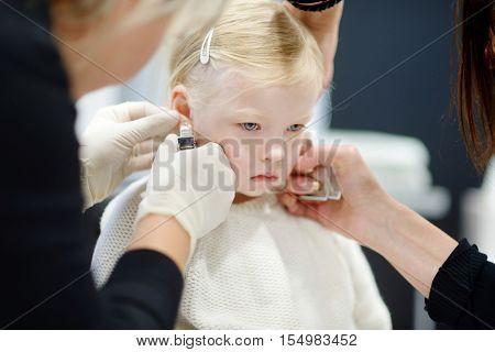 Adorable Little Girl Having Her Ears Pierced