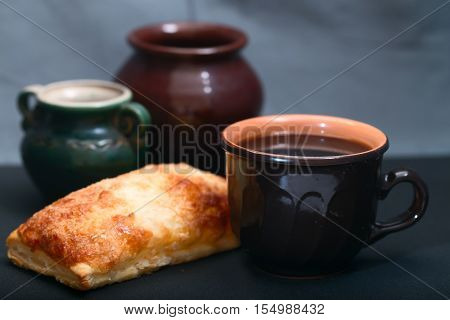 Dark ceramic ware and pie. Close up dark background small depth of sharpness