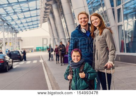 Organized and ready to go. Cropped shot of happy family standing outdoor near entrance of airport and waiting for taxi arrival
