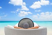 Travel vacation woman relaxing lying down on sun bed sofa lounge chair on holidays. Sleeping person  poster