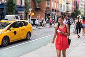 Woman walking in new york city using phone app for taxi ride hailing service or playing online game  poster