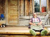 stock photo of gad  - Elderly woman in front of her old house - JPG