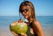 Attractive Woman Drinking Coconut Water On The Beach poster