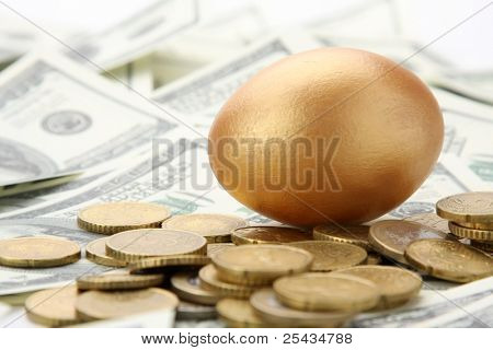 A gold egg lying on dollars and coins