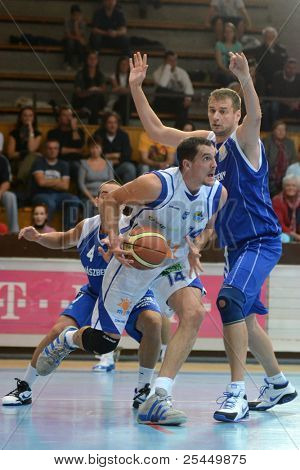KAPOSVAR, HUNGARY - OCTOBER 15:Jozsef Lekli (in white) in action at a Hugarian National Championship basketball game Kaposvar (white) vs. Jaszbereny (blue) on October 15, 2011 in Kaposvar, Hungary.