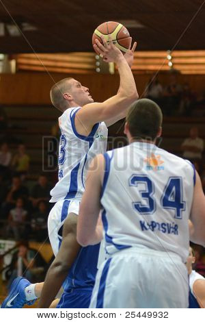KAPOSVAR, HUNGARY - OCTOBER 15: Nik Raivio (with ball) in action at a Hugarian National Championship basketball game Kaposvar (white) vs. Jaszbereny (blue) on October 15, 2011 in Kaposvar, Hungary.